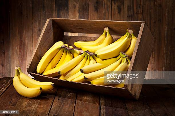 Bananas in a crate on rustic wood table