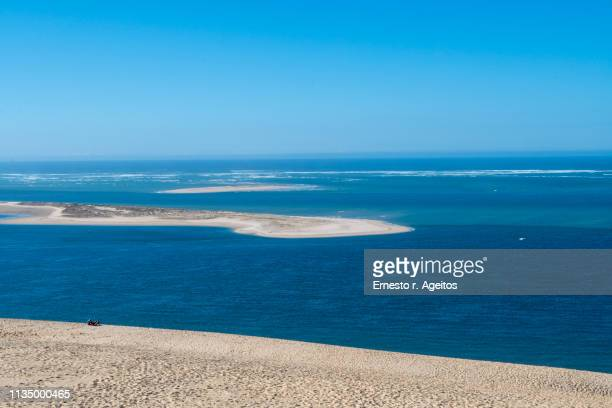 banc d'arguin view from the top of dune of pylat, france, with a couple sunbathing on the sand - gironde stock pictures, royalty-free photos & images