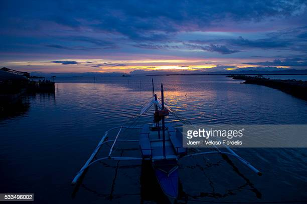 banca or philippine outrigger docked at sunset (cordova, mactan island, cebu) - joemill flordelis stock pictures, royalty-free photos & images
