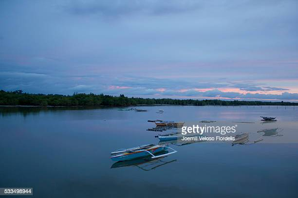 bancas or philippine outriggers docked at sunset (cordova, mactan island, cebu) - joemill flordelis stock pictures, royalty-free photos & images