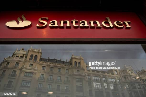 Banco Santander's logo stands on a bank's office as a building is reflected on its window a day before a news conference to announce the 2018 results...