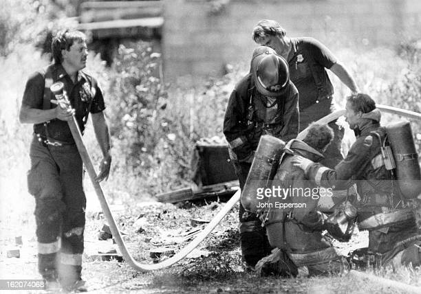 JUL 26 1988 Bancroft firefighters take a short break at the scene of a hot smokey fire at an abandoned house located near Dartmouth and Wadsworth in...