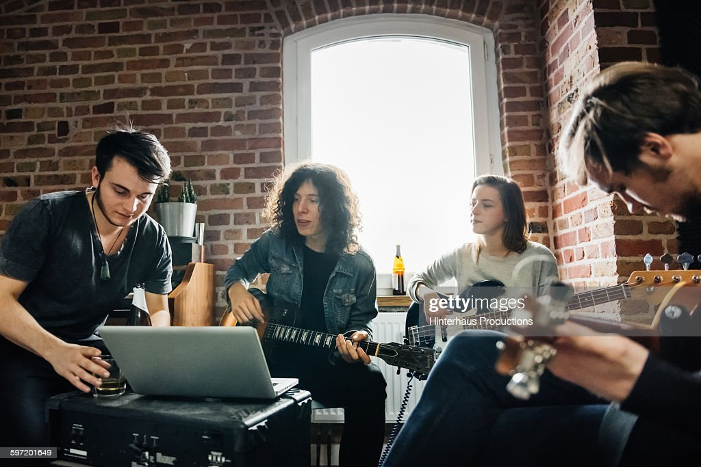 Four members of a band composing and performing a new song in a small record studio