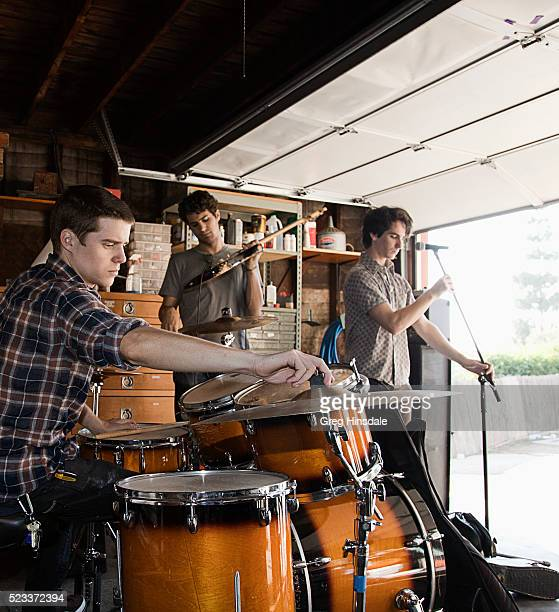band installing musical equipment in garage - garage band stock photos and pictures