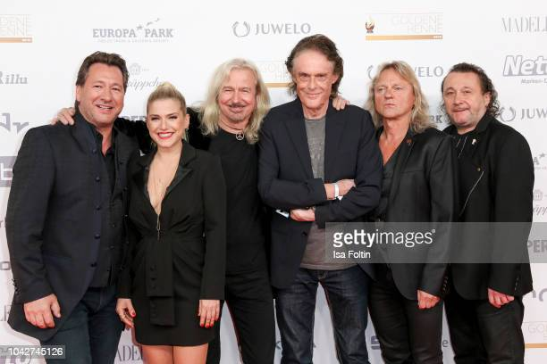 Band Karat members Claudius Dreilich Bernd Roemer Christian Liebig and Martin Becker with German singer Jeanette Biedermann during the Goldene Henne...