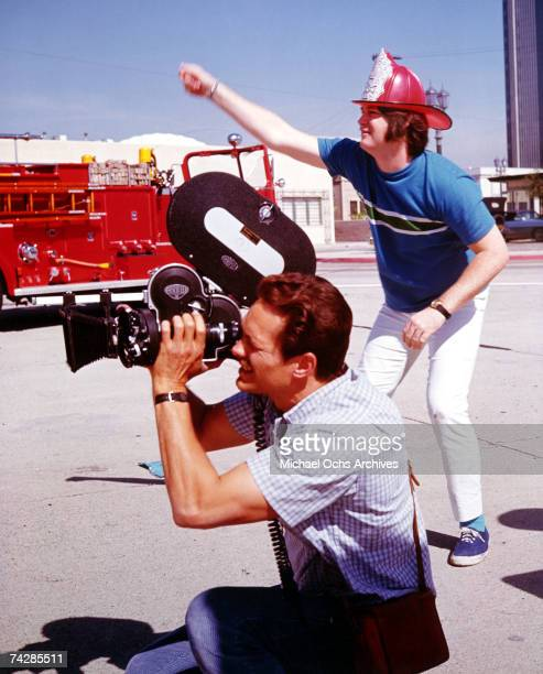 Band leader Brian Wilson of the rock and roll band 'The Beach Boys' directs the 'Good Vibrations' promo film as a he wears a fireman's hat and a...