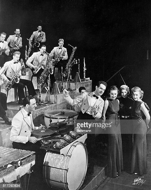 Band leader Fred Waring directs his orchestra as the Lane Sisters sing