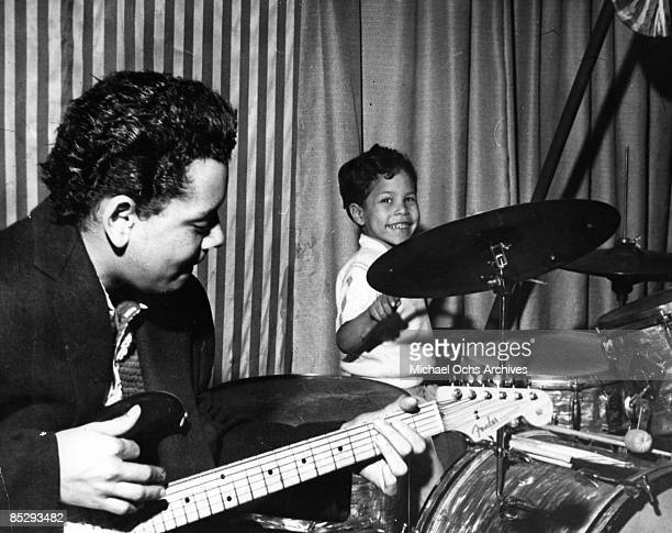 Band leader Johnny Otis plays a Fender Stratocaster electric guitar as he performs onstage with his young son Shuggie Otis on the drums in 1957.