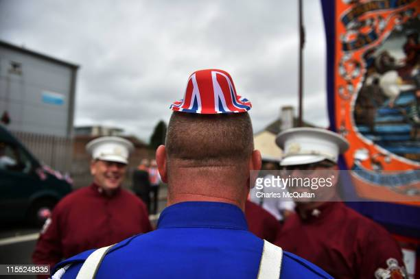 A band member wears a novelty union jack hat as Orangemen take part in the annual Twelfth of July Orange demonstration march on July 12 2019 in...