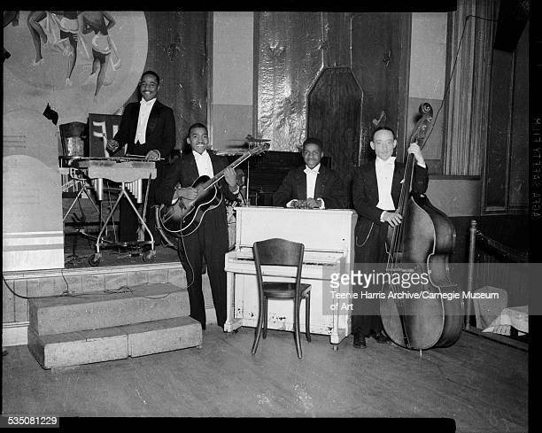 Band members including James 'Honey Boy' Minor on percussion Joe Westray on electric guitar Erroll Garner behind piano and George 'Ghost' Howell on...