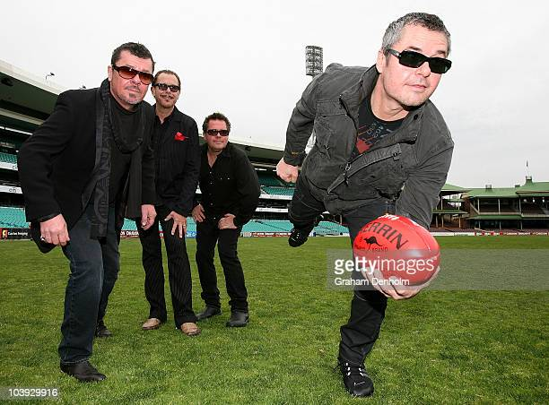 INXS band members Tim Farriss Kirk Pengilly and Andrew Farriss look on as Jon Farriss makes a pass with an AFL ball following the announcement that...