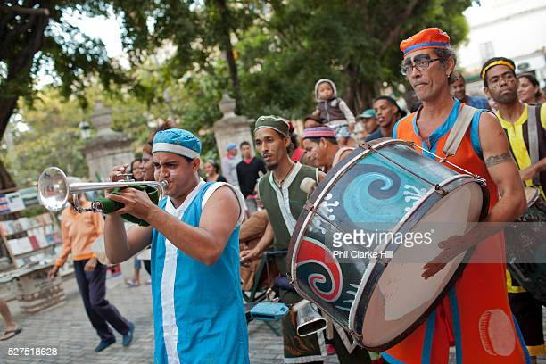 A band of Cubans play traditional music in the street wearing costumes drumming and dancing Havana old town
