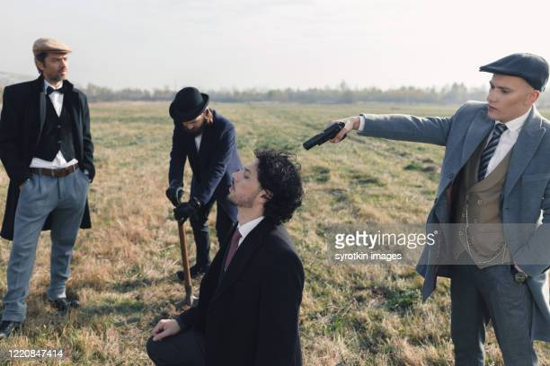 band of gangsters pointing gun at back of head of man. - dead gangster stock pictures, royalty-free photos & images