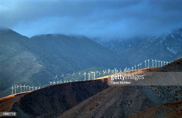 Band of sunlight shines through storm clouds to illuminate wind generators at a wind farm on December 17, 2002 near Palm Springs, California while...