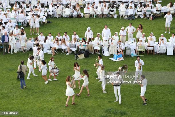 A band perform as people dressed in white gather for a diner during the 30th edition of the 'Diner en Blanc' event on the Invalides esplanade in...