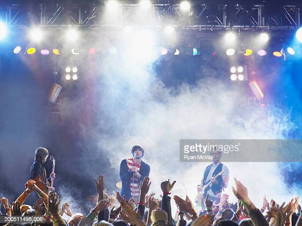 Band performing on stage, audience holding up hands in foreground