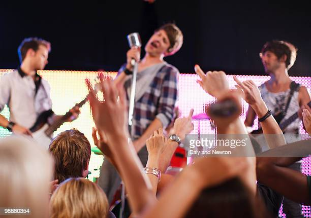 band performing on stage, crowd in foreground - pop music stock pictures, royalty-free photos & images