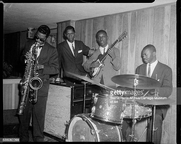 Band performing with Rashaan Roland Kirk playing three different saxophones Jerry Byrd on guitar Wendell Byrd on organ and man on drums in club with...