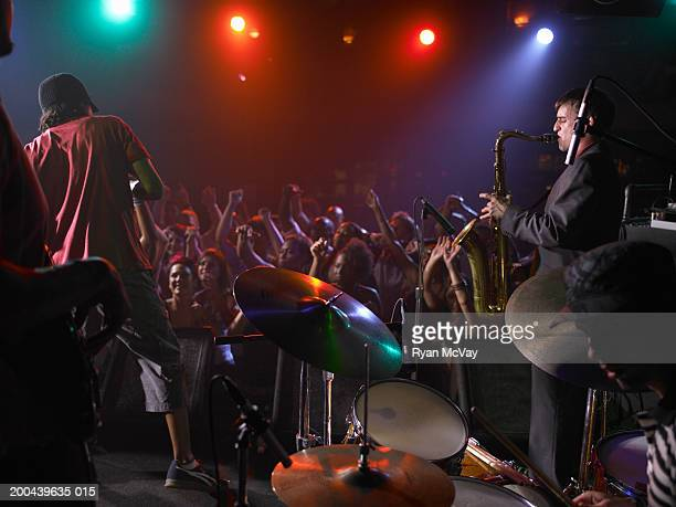 band playing music on stage in nightclub, crowd cheering - performance group stock pictures, royalty-free photos & images