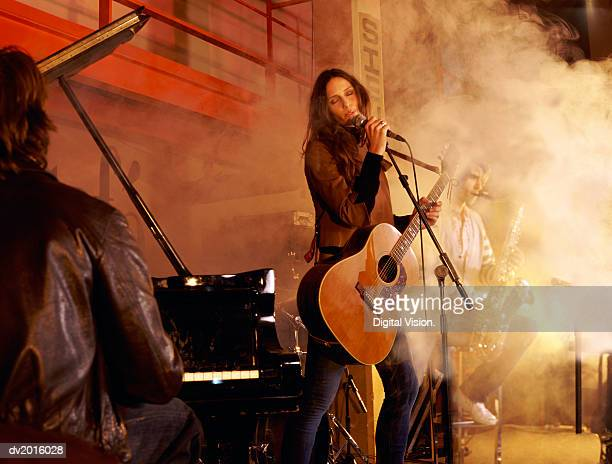 band playing on a smokey stage - microphone stand stock photos and pictures