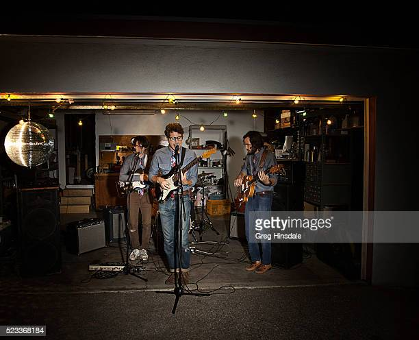 band rehearsing in garage - garage band stock photos and pictures