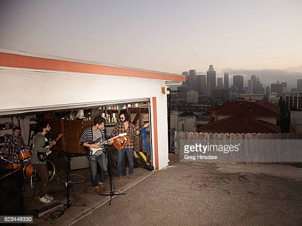 band rehearsing in garage with city skyline - garage band stock photos and pictures