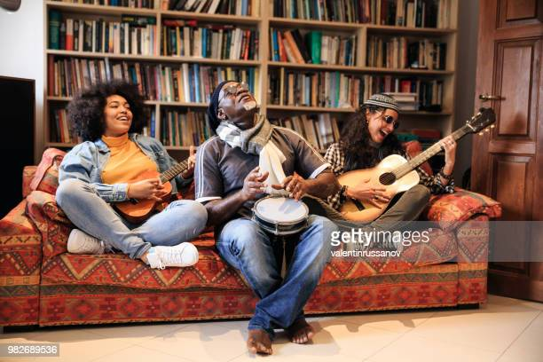 band sitting on sofa and playing instruments - garage band stock photos and pictures