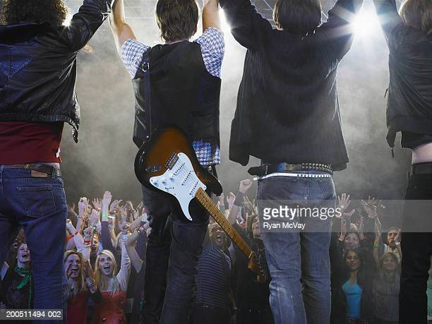 Band standing before audience on stage, arms raised, rear view