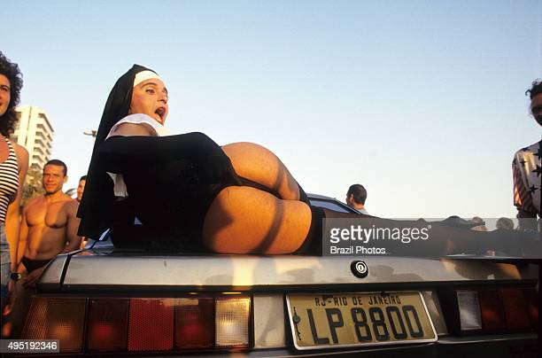 Banda de Ipanema gays wearing costumes have fun and enjoy Rio de Janeiro street Carnival Gay man dressed up as sister over car Banda de Ipanema is...