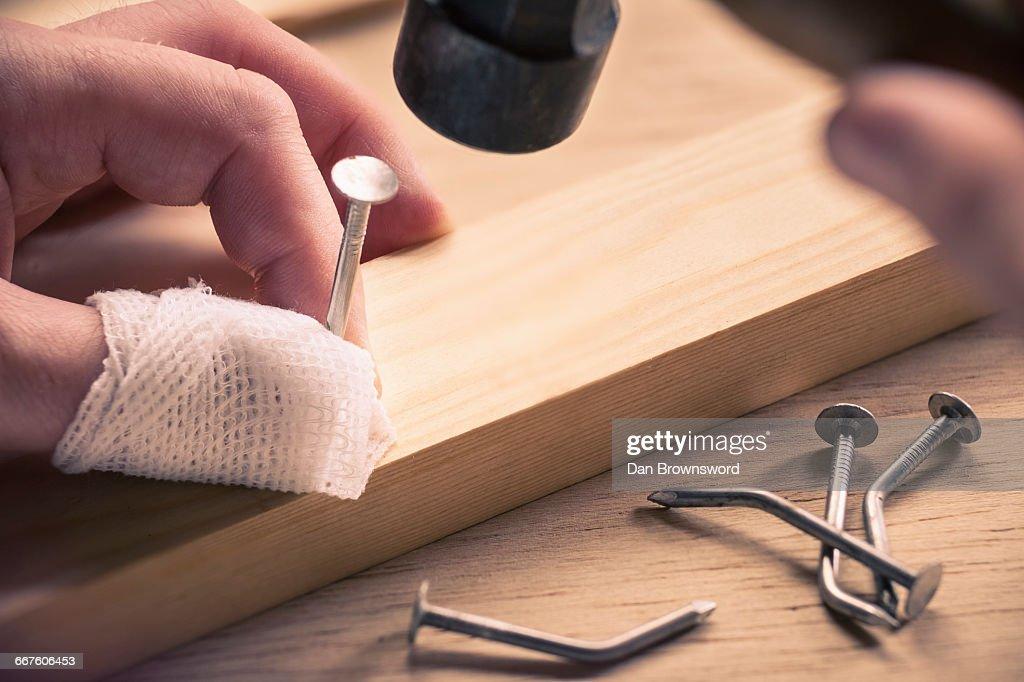 Bandaged finger holding nail on wood : Stock Photo