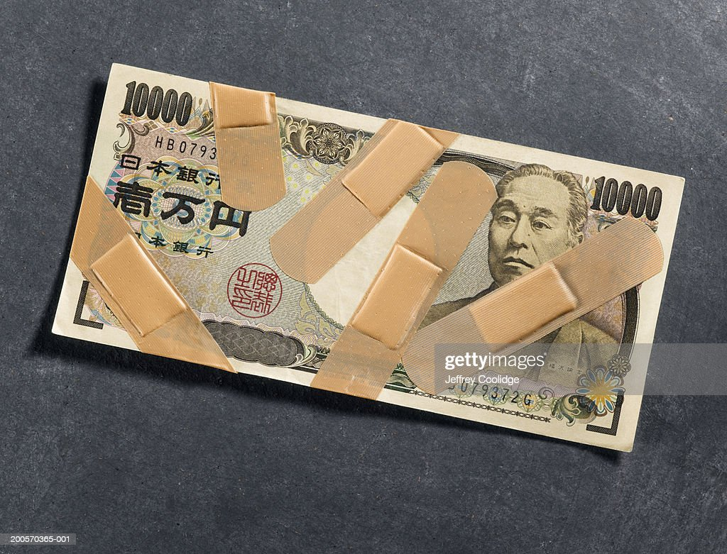 Bandages on ten-thousand-yen note, overhead view : Stock Photo