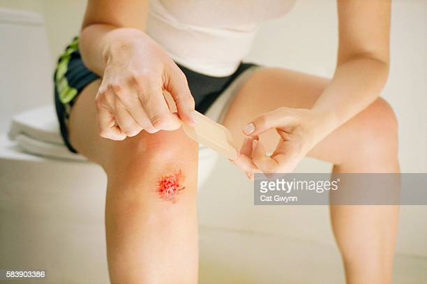 bandaging a scraped knee - healing wound stock pictures, royalty-free photos & images