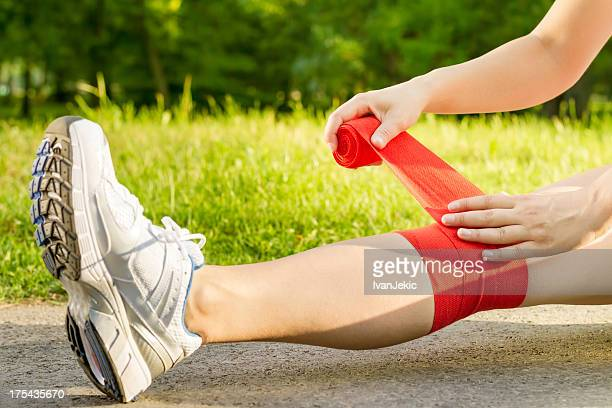 bandaging the knee outdoors - swollen ankles stock pictures, royalty-free photos & images