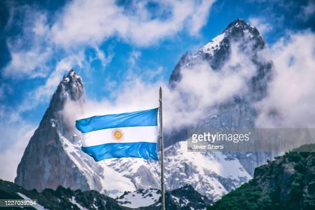 bandera argentina y aguja poincenot (a la izquierda) y cerro chaltén o monte fitz roy (a la derecha), de fondo. santa cruz, argentina. - bandera argentina fotografías e imágenes de stock