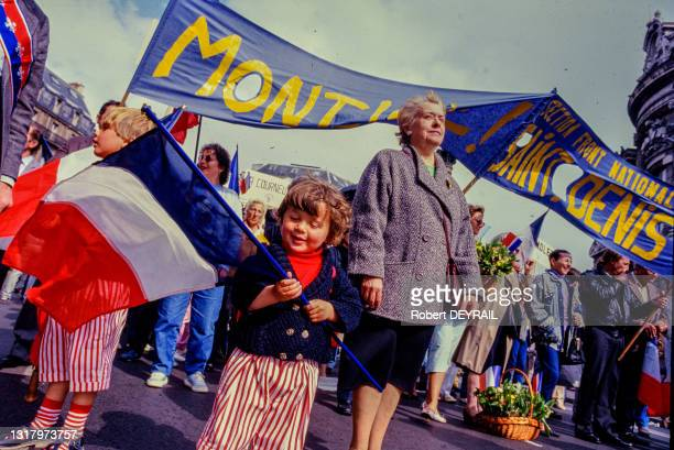 """Banderole """"MONT JOIE SAINT DENIS"""", vendeurs de muguet et enfants tenant un drapeau français lors du premier défilé en hommage au travail et à Jeanne..."""