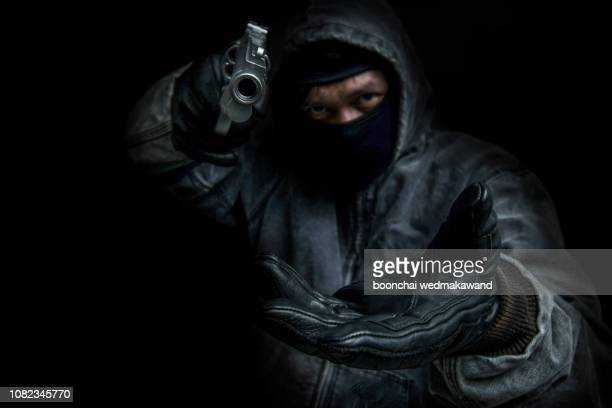 bandit carrying a gun, wearing a black mask, robbed. - image - black mask disguise stock pictures, royalty-free photos & images