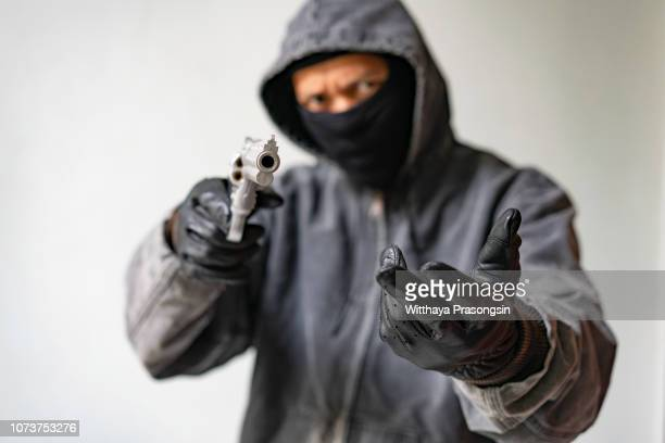 bandit carrying a gun, wearing a black mask, robbed. - thief stock pictures, royalty-free photos & images