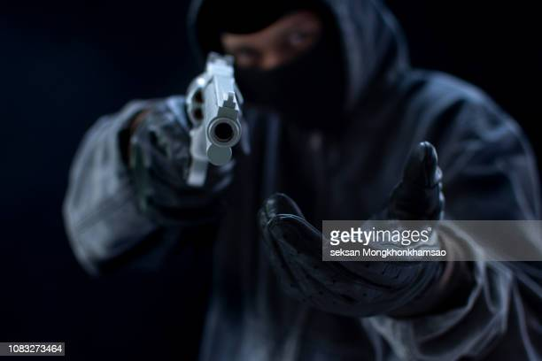 bandit carrying a gun, wearing a black mask, robbed. - black mask disguise stock pictures, royalty-free photos & images