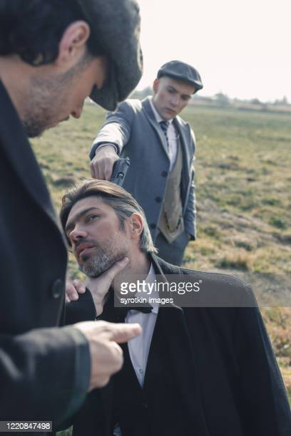 bandit putting gun to head of male. - dead gangster stock pictures, royalty-free photos & images