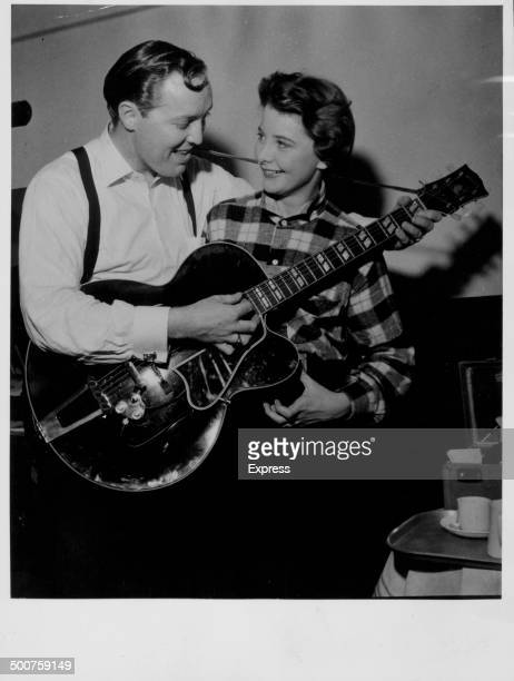 Bandleader Bill Haley teaching actress June Thorburn how to play the guitar London England February 16th 1957