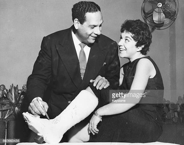 Bandleader Edmundo Ros signing the plaster cast of singer Serenella who broke her leg on stage in Madrid during a trip to London September 19th 1956
