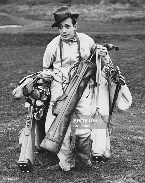 Bandleader Harry Roy acting as a caddy to his band members, dragging lots of golf clubs around the course at Whitchurch, near Cardiff, Wales,...