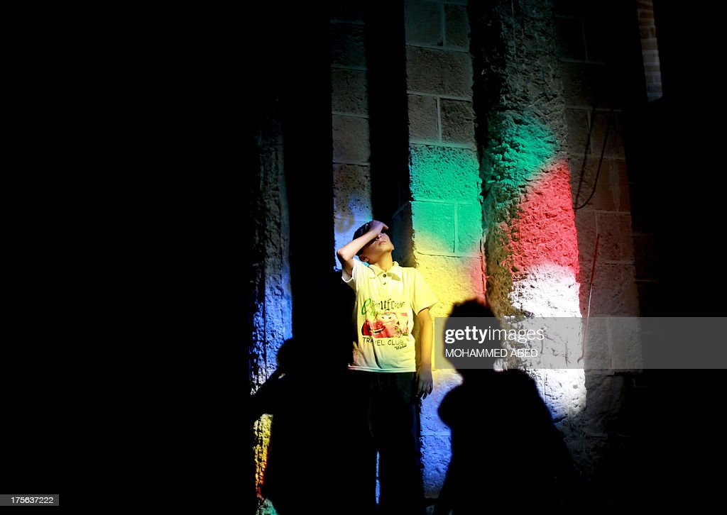 Bands of coloured light stream through reflecting on the wall of a mosque as a Palestinian boy looks up at a stained glass window, in Gaza City, on August 5, 2013. Muslims around the world are preparing to celebrate the Eid al-Fitr holiday next week, which marks the end of the fasting month of Ramadan.