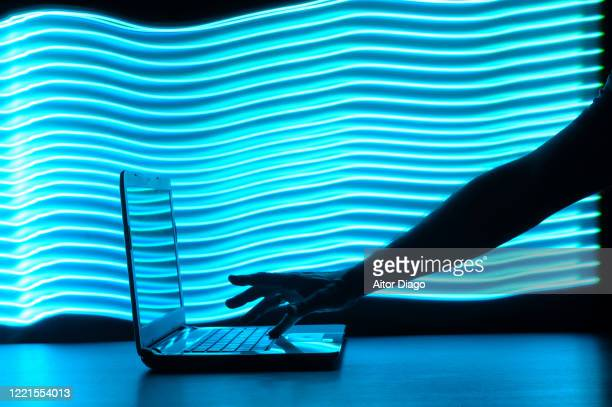 bandwidth: man's hand writing on a laptop in a futuristic environment with blue lines. - government shutdown stock pictures, royalty-free photos & images