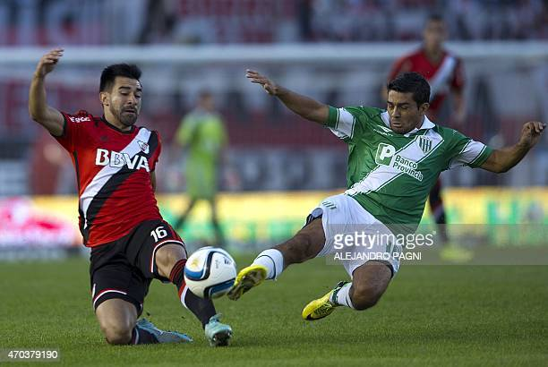 Banfield's midfielder Walter Erviti vies for the ball with River Plate's midfielder Ariel Rojas during their Argentina First Division football match...
