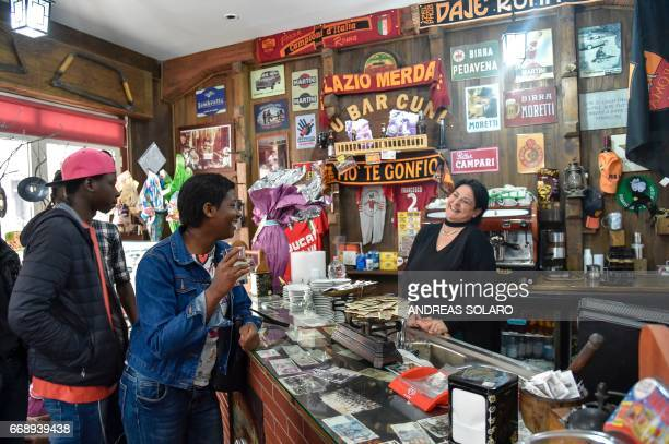 CARRIER Bangali a migrant from Senegal and Annabel from Niger joke with the waitress in the main bar of Sant' Alessio in Aspromonte a small village...