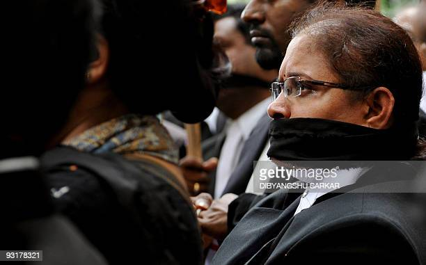 A Bangalore High Court advocate her mouth gagged with black cloth participates in a protest in Bangalore on November 18 against an attack on court...