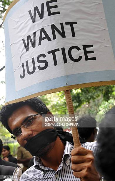 A Bangalore High Court advocate his mouth gagged with black cloth participates in a protest in Bangalore on November 18 against an attack on court...