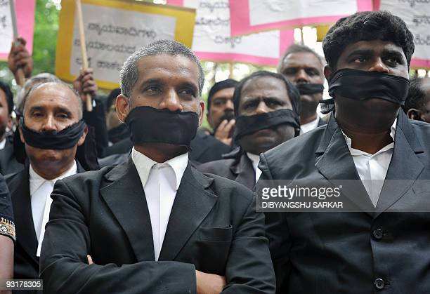 Bangalore High Court advocates their mouths gagged with black cloth stage a protest in Bangalore on November 18 against an attack on court...