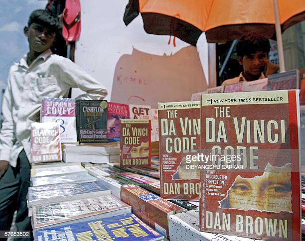 An Indian book vendor looks on as copies of 'The Da Vinci Code' are displayed on sale at his roadside book stall in Bangalore 19 May 2006 India's...